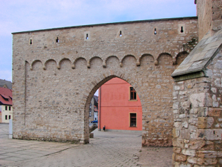Bild: Detailansicht des erhaltenen Stückes der Stadtmauer am Johannistor mit Torbogen und Schießscharten.