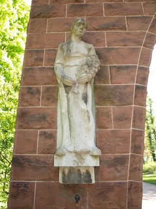 Bild: Die linke Figur am Tor der Mahnung verkörpert die trauernde Mutter oder Ehefrau - aber aufrecht und sich in das Unvermeidliche fügend.