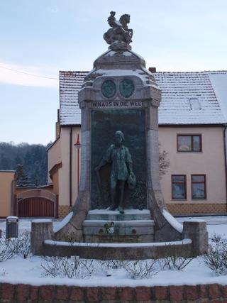 Bild: Martin Luther tritt in die Welt. Bronzerelief am Lutherbrunnen zu Mansfeld.