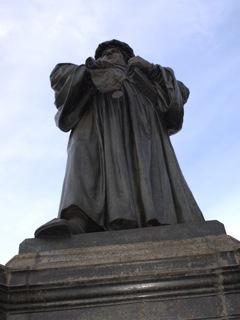 Bild: Martin Luther mit Bibel und päpstlicher Bulle. Lutherdenkmal in der Stadt Eisleben.