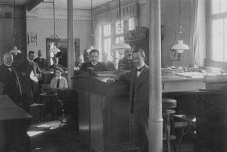 Bild: Das Büro der Metallhandlung der Mansfeldischen Kupferschiefer Bauenden Gewerkschaft im Jahre 1913. Dieses Bild ist gemeinfrei, weil seine urheberrechtliche Schutzfrist abgelaufen ist.