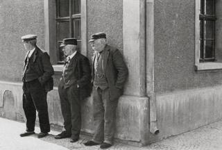 """Bild: Ein Schnappschuss bescheidenen Wohlstandes. Pensionäre der Knappschaft in Eisleben wärmen um 1900 """"ihr Fell"""" in der Sonne. Dieses Bild ist gemeinfrei, weil seine urheberrechtliche Schutzfrist abgelaufen ist."""