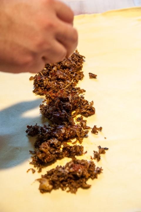 Bild: Einen Teil der abgekühlten Champignonfarce in der Breite der Filets auf dem flach ausgebreiteten Blätterteig verteilen.