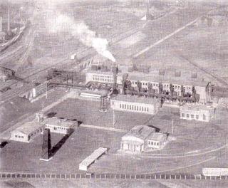 Bild: Die Bessemerei in Hettstedt in einer historischen Fotografie aus den 1940er Jahren. Auf der linken Bildseite ist die Bunkeranlage zu sehen, auf der heute der Rohsteinkran steht (Brückenkonstruktion zwischen Böschung und Rohrbrücke). Dieses Bild ist gemeinfrei, weil seine urheberrechtliche Schutzfrist abgelaufen ist.