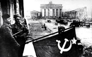 Bild: Soldaten der Roten Armee hissen die sowjetische Fahne auf dem Balkon des Hotel ADLON in der Nähe des Brandenburger Tores. Bild: Deutsches Bundesarchiv (German Federal Archive), Bild 183-R77767.