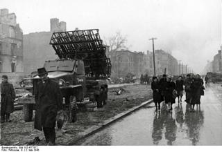 Bild: Deutsche Zivilisten in Berlin am 2. Mai 1945 unmittelbar vor der offiziellen Übergabe der Stadt durch General Helmuth Weidling. Im Hintergrund ist ein sowjetischer Raketenwerfer - auch KATJUSCHA oder STALINORGEL genannt. Deutsches Bundesarchiv (German Federal Archive), Bild 183-R77872, Autor G. Petrusow.