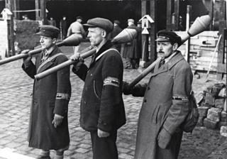 Bild: Drei Männer des Volkssturm stehen in Berlin Posten mit Panzerfaust beim Bau von Straßensperren. Bild: Deutsches Bundesarchiv (German Federal Archive), Bild 183-J31320.