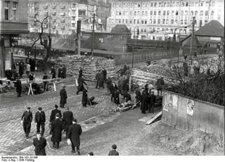 Bild: Panzersperre am S-Bahnhof Hermannplatz in Berlin-Neukölln. Volkssturmmänner sind noch mit Schanzarbeiten beschäftigt. Bild: Deutsches Bundesarchiv (German Federal Archive), Bild 183-J31386.