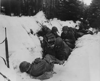 Bild: US Soldaten suchen Schutz während des Gefechtes beim Vormarsch in Deutschland. Dieses Bild wurde von einem Mitglied der United States Army während dessen Ausführung seiner Dienstpflichten erstellt. Als eine Arbeit der US-Regierung ist dieses Bild public domain.