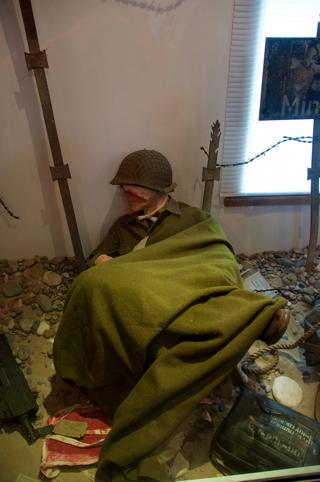 Bild: Auch auf Seiten der Alliierten gab es schwere Verluste - Ein verwundeter Infanterist der US ARMY wartet in seiner Gefechtsstellung auf Hilfe durch einen Sanitäter. Aufnahme vom BIG RED ONE MUSEUM am POINTE DU HOC - OMAHA BEACH - Normandie aus dem Jahre 2010.